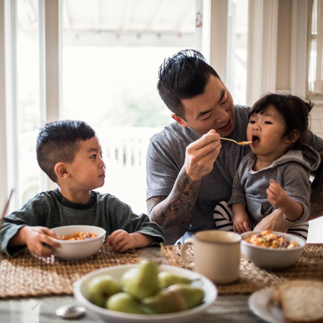 一位父亲与两个孩子一起吃早餐