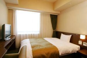 多美迎熊本天然温泉酒店客房内的一张或多张床位
